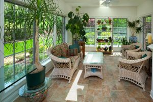 sunroom with white wicker furniture and lots of plants