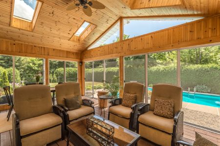 Wooden patio screened in poolside with beautiful tan and brown furniture