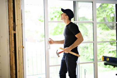 Young man installing a double sliding patio door