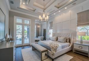 Elegant master bedroom with hinged doors leading out to a patio
